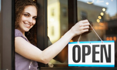 "Young Woman Hanging ""Open"" Sign Outside Store --- Image by © Flint/Corbis"